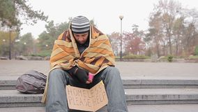 Sad male beggar sitting alone in park, warming up with old blanket, man coughing. Stock footage stock video footage