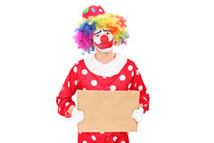 Sad male clown holding a blank carton sign Royalty Free Stock Photo
