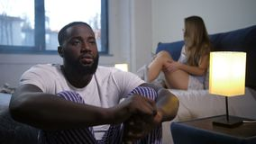 Sad male in depression distressed by unemployment. Upset african american man suffering from depression due to lack of work. Worried young woman sitting on bed stock video footage