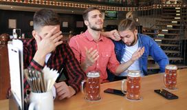 Sad male football fans watching game at bar and drinking beer.  royalty free stock images