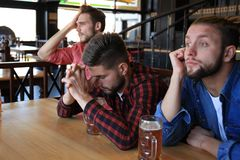 Sad male football fans watching game at bar and drinking beer.  royalty free stock photos