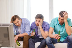 Sad male friends with beer watching sports Royalty Free Stock Images