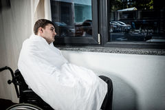 Sad male ill patient sitting by the window on wheelchair covered Stock Images