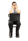 Sad male with leather suitcase sitting on a wooden chair Royalty Free Stock Image