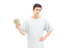A sad male patient in a hospital gown holding US dollars Royalty Free Stock Image