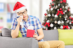 Sad male on a sofa wiping his eyes with christmas tree in the ba. Sad young male seated on a sofa wiping his eyes from crying with christmas tree in the Royalty Free Stock Photo