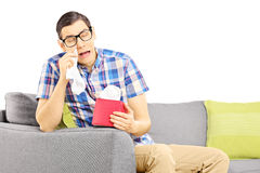 Sad male on a sofa and wiping his eyes from crying Stock Photos
