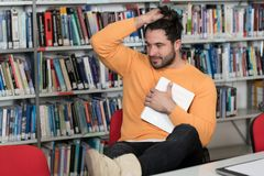 Sad Male Student in the University Library. Stressed Young Male Student Reading Textbook While Sitting in Library Royalty Free Stock Images