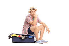 Sad male tourist sitting on bag full of clothes Stock Images