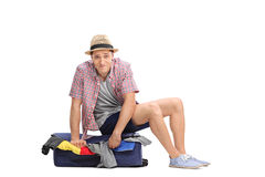 Sad male tourist sitting on top of a packed suitcase Royalty Free Stock Images