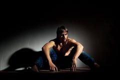 Sad man. Sitting on floor in a dark room Stock Photo