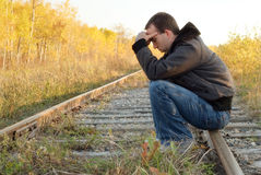 Sad Man. A sad man sitting on a set of railroad tracks doing some thinking Stock Photo