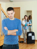 Sad man against wife with baby and suitcase Stock Photo