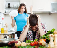 Sad man with angry wife at kitchen. Sad men with angry wife at kitchen. Focus on guy stock photo