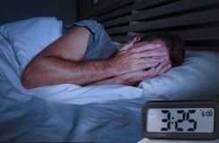 Sad man awake lying sleepless on bed covering his eyes crying suffering insomnia sleeping disorder with alarm clock stock image
