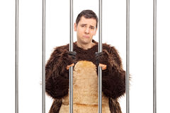Sad man in a bear costume standing behind bars Royalty Free Stock Photography