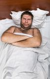 Sad man in bed with crossed hands Royalty Free Stock Photography