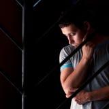 Sad man behind bars thinking about something.  stock image