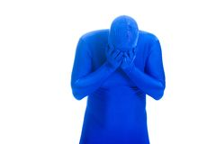 Sad man in blue body suit crying in his hands. Stock Photo