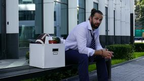 Sad man with the box. Sad jobless man sitting on bench near by office stock video footage