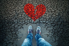 Sad man with broken heart background. Lonely man standing on cracked asphalt floor with illustrated cracked broken heart symbol. Point of view perspective used stock photography