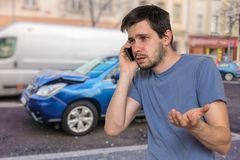 Sad man is calling to assistance after car accident stock image