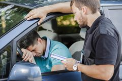 Sad man in car. Sad young men in car fined by police officer Royalty Free Stock Image
