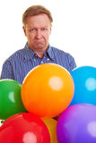 Sad man with colorful balloons Royalty Free Stock Images
