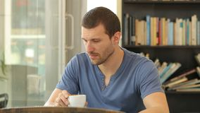 Sad man complaining in a coffee shop. Sad man complaining holding coffee cup sitting in a restaurant stock video