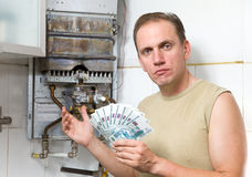 The sad man counts money for repair of a gas water. Heater Royalty Free Stock Photo