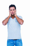 Sad man covering his ears and looking at camera Royalty Free Stock Photography
