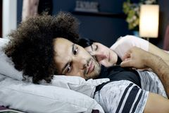 Sad man almost crying in bed holding hand of girlfriend royalty free stock image