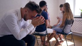 Sad man crying and covers face with hands on group therapy session on background of people sitting on chairs in circle stock video footage