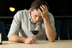 Sad man drinking wine in a bar. Sad man complaining and drinking wine alone in a bar in the night Stock Images