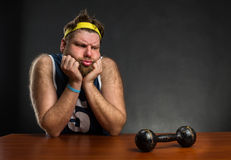 Sad man with a dumbbell. Sad man looking at dumbbell at the table stock image