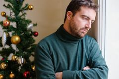 Sad man feeling negative emotions and alone during christmas royalty free stock images