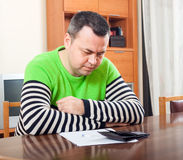 Sad man filling financial documents. Serious man counting his money at table at home royalty free stock photo