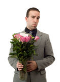 Sad Man With Flowers. A young man holding a vase of roses with a sad expression on his face, isolated against a white background royalty free stock photo