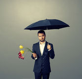 Sad man with flowers Stock Image