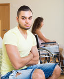 Sad man with girlfriend in invalid chair Royalty Free Stock Photography