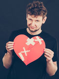 Sad man with glued heart by plaster. Stock Photography