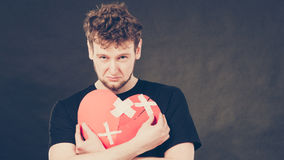 Sad man with glued heart by plaster. Royalty Free Stock Image