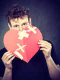 Sad man with glued heart by plaster. Stock Image