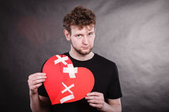 Sad man with glued heart by plaster. Royalty Free Stock Images