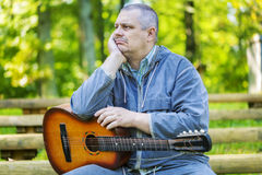 Sad man with guitar in park on bench Royalty Free Stock Photos