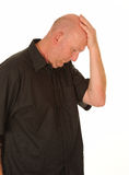 Sad man with hand on head. Side half body portrait of sad middle aged man with hand on bald head, white studio background Stock Photos