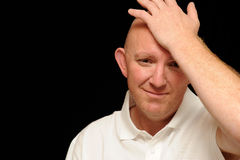 Sad man with hand on head. Sad looking bald man holding hand on his head, black background Royalty Free Stock Image