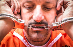 Sad Man with Handcuffs in Prison. Close Up portrait of a detained man with handcuffs between the lips for the sadness Royalty Free Stock Photography