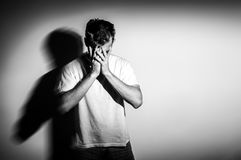 Sad man with hands on face in sadness, on white background, black and white photo, free space. Sad man with hands on face in sadness, on white background, black Royalty Free Stock Image