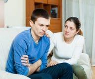 Sad man has problem, woman consoling him. Sad men has problem, women consoling him on sofa at home Stock Images
